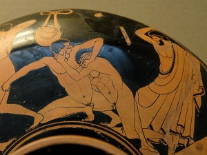 Escena de Pancracio. El árbitro se dispone a azotar con un látigo al luchador que ha metido el dedo en el ojo de su adversario. Kílix, siglo V a. C., British Museum.
