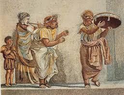 Mosaico romano, firmado por Dioscorides de Samos, s. I a. C., Museo Nacional de Nápoles. En él se representa una escena cómica, en la que participan tres músicos con máscara, que tocan diversos instrumentos (una flauta doble -(αὐλός/aulós)-, unos platillos y un pandero grande), y un niño o enano, sin máscara, que lleva un cuerno en la mano.