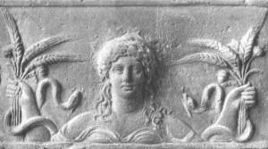 Cabeza de Deméter, con dos de sus principales atributos: ramo de espigas con adormideras y serpientes. Relieve en tierra cocida. Museo de las Termas, Roma.